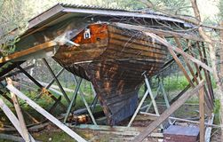 Boat house that collapsed over a wooden boat royalty free stock image