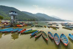 Boat house of colorful Nepal boats in Pokhara Nepal. Boat house colorful Nepal boats Pewa Lake background green hills and mountain in Pokhara Nepal royalty free stock image