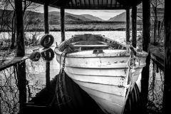 Boat House in on an Irish lake. This is a solitary white rowboat in a boat house on a Donegal lake in Ireland stock photos