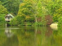 Boat House on a lake. A timber boat house standing beside a lake Stock Image