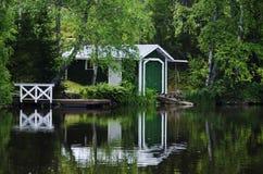 Boat house reflecting on lake Royalty Free Stock Photos