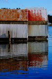 Boat house reflections. Two rustic boat houses cast reflections on the water Stock Image