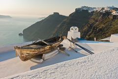 Boat on a house roof at sunset in front of Skaros rock at Imerovigli village, Santorini island Royalty Free Stock Photo