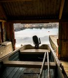 Boat house with a small boat with motor and oars, seen from the inside, looking out at the ocean. Boat house with a small boat, seen from the inside, looking Stock Photo