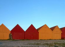 Boat Houses. In orange and red against a light blue sky Stock Image