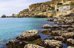 Rocky coastline shoreline. Boat houses at Golden Sands Bay on the Maltese islands Stock Images