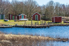 Boat houses. Red wooden boat houses with wooden bridges in front. Ocean and dry vegetation in foreground. Sunshine in early spring. Up side down boats on land Stock Photos