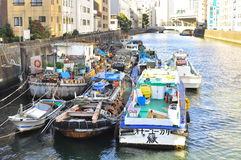 Boat houses at Sumida River of Tokyo. A view of city canals in Tokyo near the Sumida river where boats and river way are still one of the active transportation Stock Images