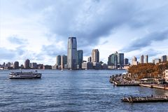 Boat on Hudson River with Pedestrian Walkway. Boat and Hudson river with pedestrian walkway and New York CIty building in background during summer day stock images