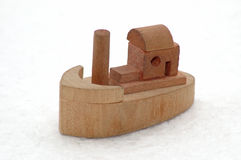 Boat on ice. Macro of a tiny wooden boat toy on white plastic, like ice. Embedded isolating clipping path Royalty Free Stock Image