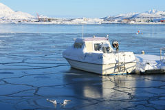 Boat on icy bay. Boat on an icy bay of Busknes fjord, lofoten islands stock photo