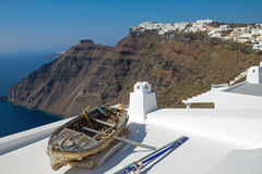 Boat and Imerovigli. An old boat on a roof and Imerovigli in the back, Santorini island, Greece Royalty Free Stock Images