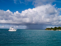 Boat Incoming Tropical Storm. Fishing boat just off the shore of a Caribbean island waits in the sun for an oncoming rainstorm Stock Photography