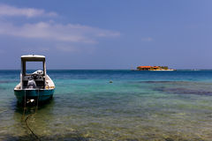 Boat and Island in the calm Caribbean sea Royalty Free Stock Image