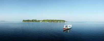 Boat and island panorama. Panoramic view of a distant island and a small boat on water Stock Image