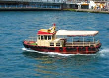 Boat in Istanbul. Red boat cruising in Istanbul off Karakoy coast Stock Photo