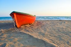 The boat on Kaiafas beach, Greece. The small boat on the deserted sandy Kaifas beach at sunset, Greece stock photography