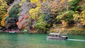 Boat at Katsura river in autumn, Arashiyama. Tourist boat sailing at Katsura river with Autumn foliage colors in Arashiyama, Kyoto, Japan. Here is famous travel Stock Photography