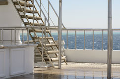 Boat ladder, Deck on the stern of the yacht on a sunny day and beautiful blue sea water. Royalty Free Stock Photos