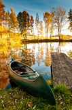 Boat at a lake. A boat at the shore of a lake. It is autumn. The trees have red and yellow leaves Royalty Free Stock Photography