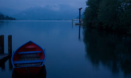 Boat on a lake. Red boat on a lake in the evening time Stock Photography