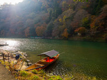 Boat in a lake in autumn landscape, yellow, orange and red Autumn trees and leaves ,Colorful foliage in the Autumn park. At Kyoto, Japan Stock Image