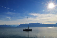 Boat on lake in the backdrop of the Alps. Royalty Free Stock Photo
