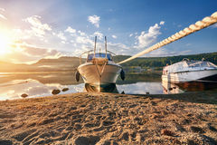 Boat on lake at background of sunset in a clear summer day. Warm summer evening on the dock near the boat. Fabulous views. Of the lake in the sun rays Royalty Free Stock Photo