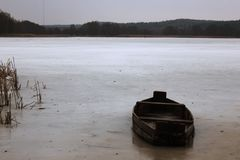 Boat on the lake covered with ice stock image