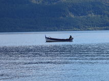 Boat on a lake. Fisherman in a Boat on Loch Ness, Scotland Royalty Free Stock Photo