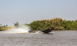 Boat at lake Inle. A boat is speeding home from the market at Inle lake, Myanmar. In the background are the mountains Royalty Free Stock Photos