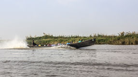 Boat at lake Inle. A boat is speeding home from the market at Inle lake, Myanmar. People and goods are at board Stock Photography