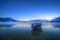 Boat In The Lake. Boat is leaning on the lake in the early of the dawn stock photography