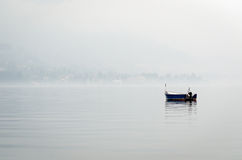 Boat on a lake with misty air Royalty Free Stock Image