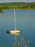 Boat on a Lake. Boat mooring with her fore to a buoy on a lake with cottages in background Stock Photo