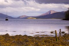 Boat on lake with mountains. Evening light falls on the distant cullin hills. The photo is taken over a tranquil loch with the water reflecting the scene. A Royalty Free Stock Photography