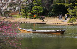 Boat on the lake. Plum blossom as foreground, a boat floating on the lake Stock Photos