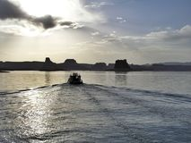 Boat on Lake Powell. Boat moving toward the sun on Lake Powell Royalty Free Stock Photos