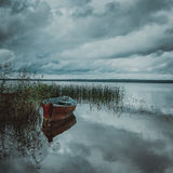 Boat on lake with a reflection trees and barn Royalty Free Stock Photo