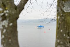 Boat on lake seen through tree bench in winter stock images
