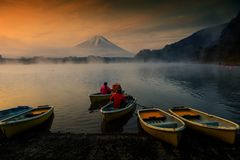 Boat at Lake Shoji with mt. Fuisan at dawn. Fisherman Sailing boat to Lake Shoji in the morning with mist , twilight sky, ad mount Fujisan or Fuji during sunrise Royalty Free Stock Photos