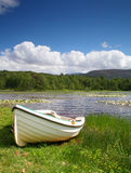 Boat on lake shore. A small lake in the Highlands of Scotland known as The Lily Loch Royalty Free Stock Images