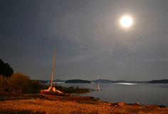 Boat on a lake shore at night in the moonlight Stock Images