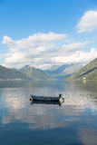 Boat on lake. Small boat on Kotor bay, Montenegro with blue skies and clouds above Stock Images