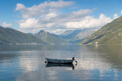 Boat on lake. Small boat on Kotor bay, Montenegro with blue skies and clouds above Royalty Free Stock Photos