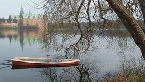 Boat lake. Smalle boat filled by wather Frederiksborg castle Stock Photo