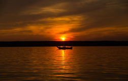 Boat on lake at sunset Royalty Free Stock Photos