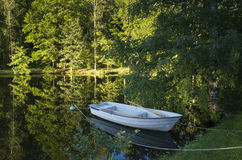 Boat at lake in Sweden. Scandinavia Europe. Beautiful nature and landscape photo. Warm summer evening. Calm and peaceful outdoors image. Forest, trees and royalty free stock image