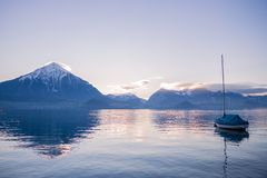 Boat on a lake in Switzerland, with a snowy mountain and clouds in the background. royalty free stock image
