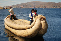 The boat on Lake Titicaca in Peru. Islanders rowing a boat on Lake Titicaca in Peru Royalty Free Stock Images